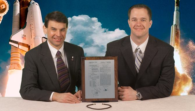 Steinetz and Dunlap are pictured with their thermal barrier and patent. Credit: NASA