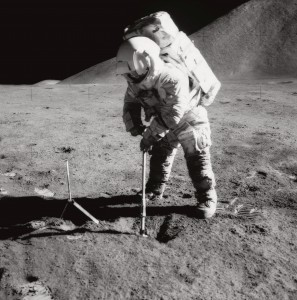 Astronaut James B. Irwin, lunar module pilot, uses a scoop to make a trench in the lunar soil during Apollo 15 EVA. Mount Hadley rises above the plain in the background.
