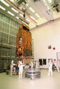 While a crane lifts NASA's FUSE satellite, workers at Hangar AE, Cape Canaveral Air Station, help guide it toward the circular payload-attach fitting in front of it.
