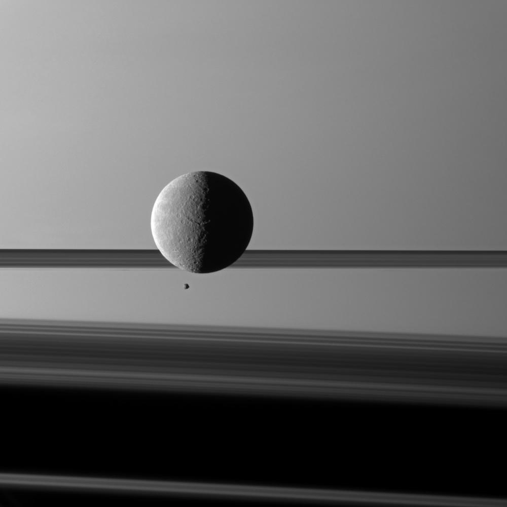 "Saturn's moon Rhea looms ""over"" a smaller and more distant Epimetheus."