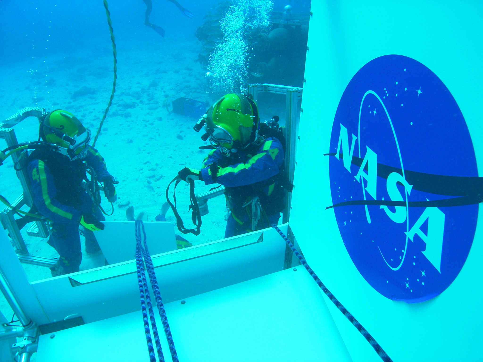 NASA Aquanaut crew performing demonstration of incapacitated crewman recovery on the side hatch of the SEV during the NEEMO 14 mission.