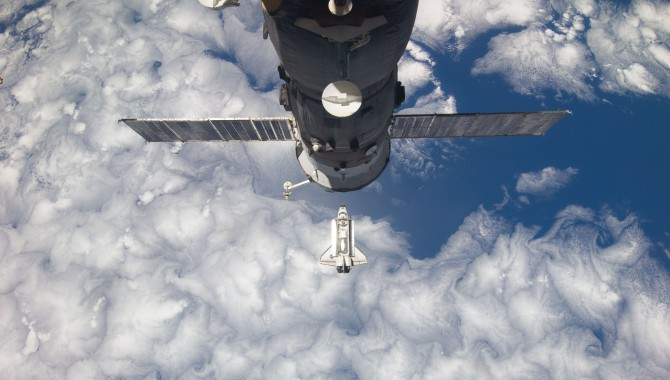 Backdropped by Earth, Discovery approaches the International Space Station