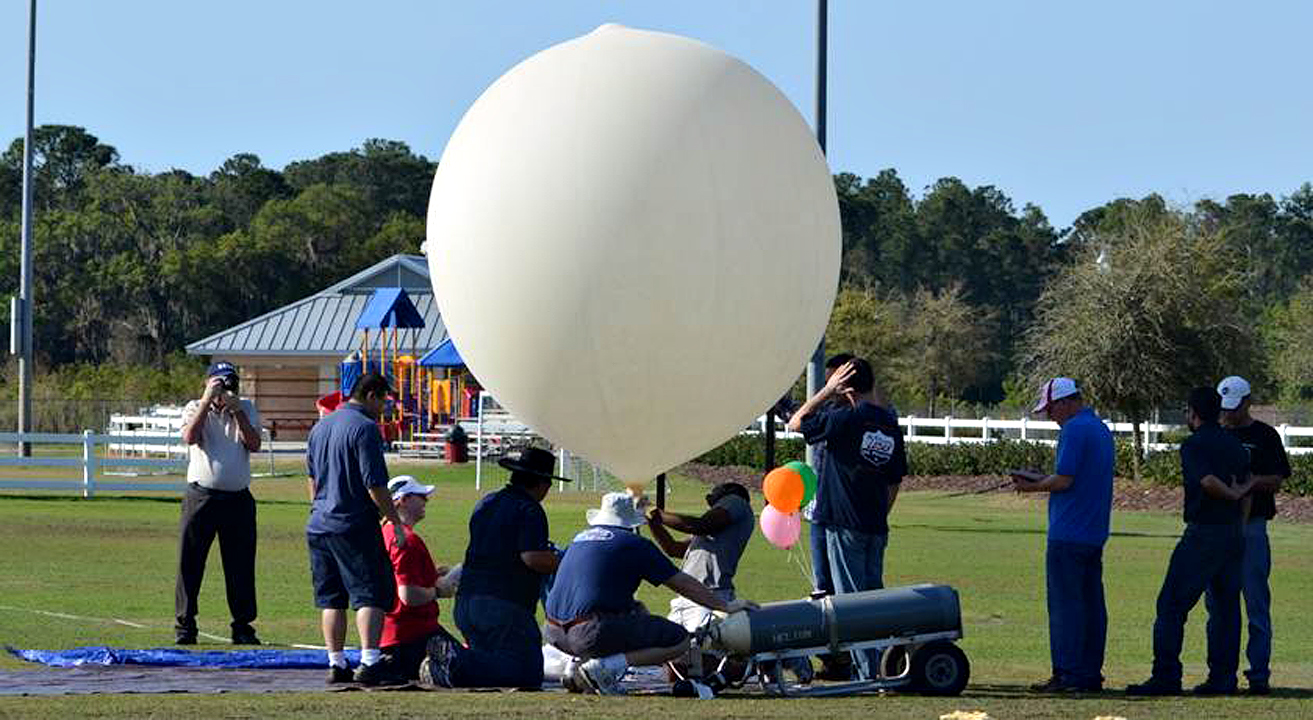 Students fill a balloon for the team's project test flight with the Rocket University payload launch and recovery lab.