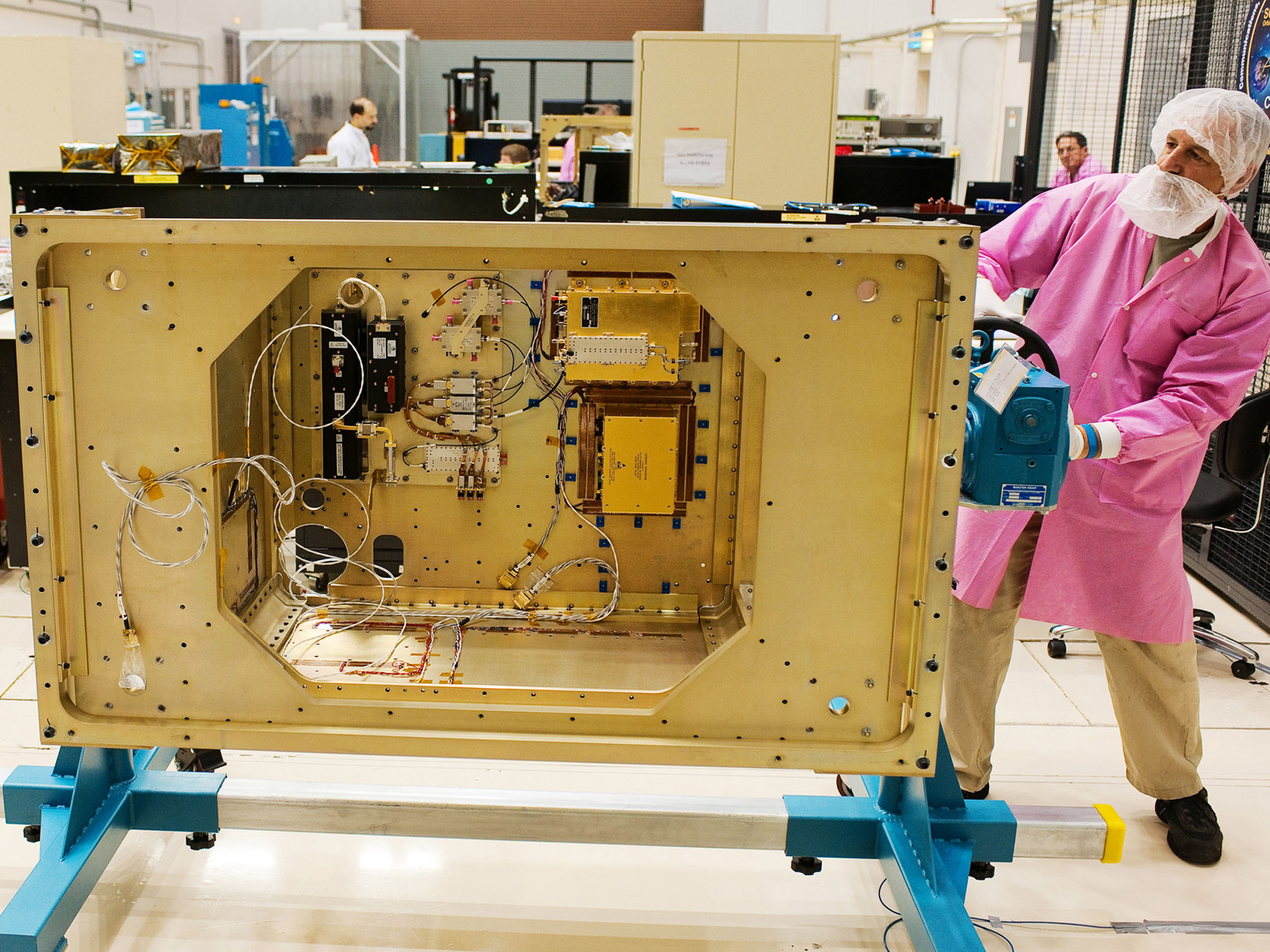 Software engineers work in the background as Glenn Research Center technician Joe Kerka rotates the SCaN Testbed flight-enclosure assembly using a specially manufactured mount.
