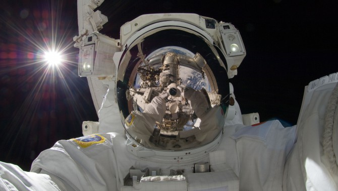 Japan Aerospace Exploration Agency astronaut Aki Hoshide, Expedition 32 flight engineer, uses a digital still camera to expose a photo of his helmet visor during the mission's third session of extravehicular activity.