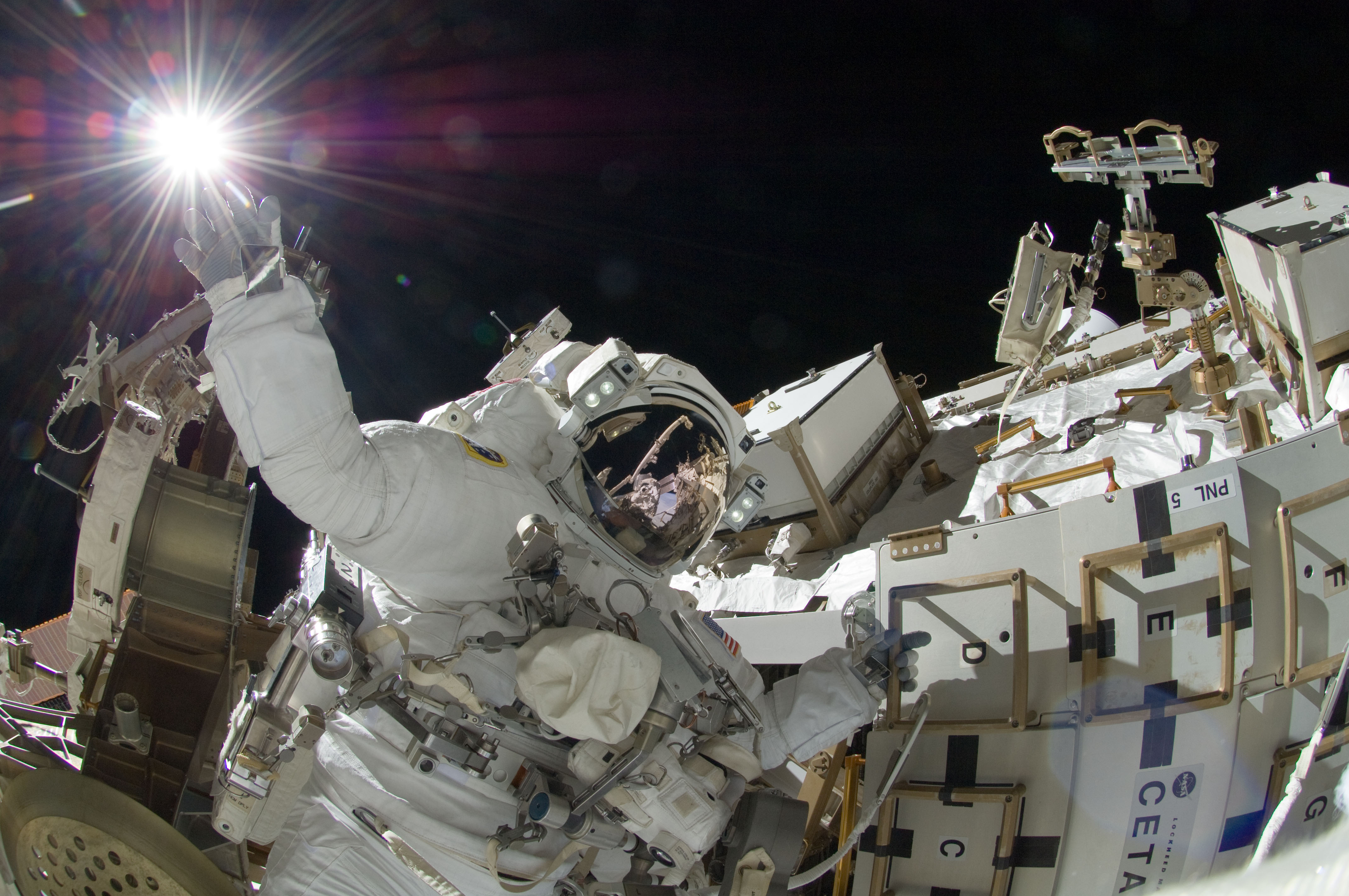 NASA Astronaut Sunita Williams appears to touch the bright sun during a third session of extravehicular activity. Williams and Japan Aerospace Exploration Agency Astronaut Aki Hoshide (visible in the reflections of Williams' helmet visor) completed installation of a main bus switching unit. Photo Credit: NASA