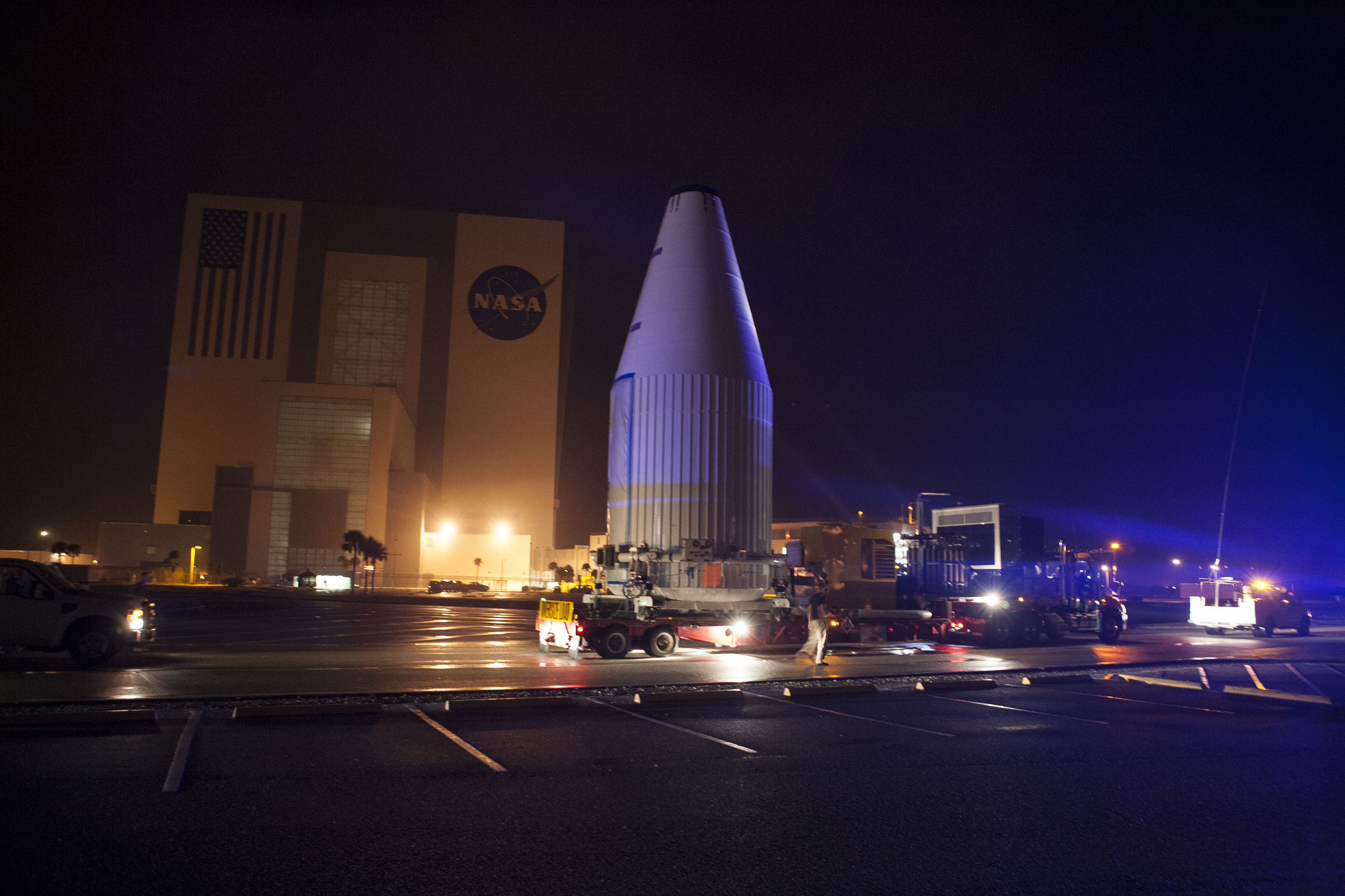 Tracking and Data Relay Satellite-K, enclosed in its payload fairing, passes through the Launch Complex 39 area and Vehicle Assembly Building at Kennedy Space Center as it travels from the Astrotech payload processing facility to its launch site.