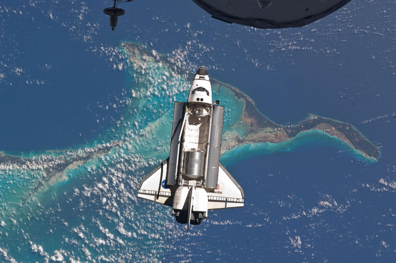 Space shuttle Atlantis is seen over the Bahamas prior to a perfect docking with the International Space Station at 10:07 a.m. (CDT). Part of a Russian Progress spacecraft which is docked to the station is in the foreground.