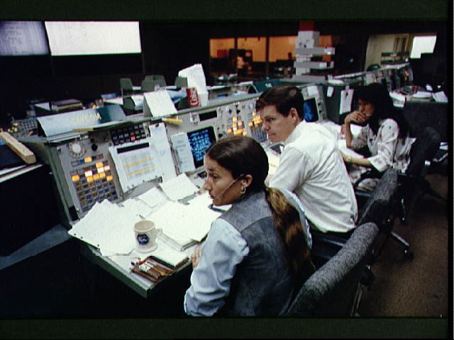 Astronauts Mary L. Cleve and Bryan D. O'Connor look toward the camera during an integrated simulation for the STS-6 mission. The two are at the spacecraft communicator (CAPCOM) console in the mission operations control room (MOCR) of the JSC mission control center.
