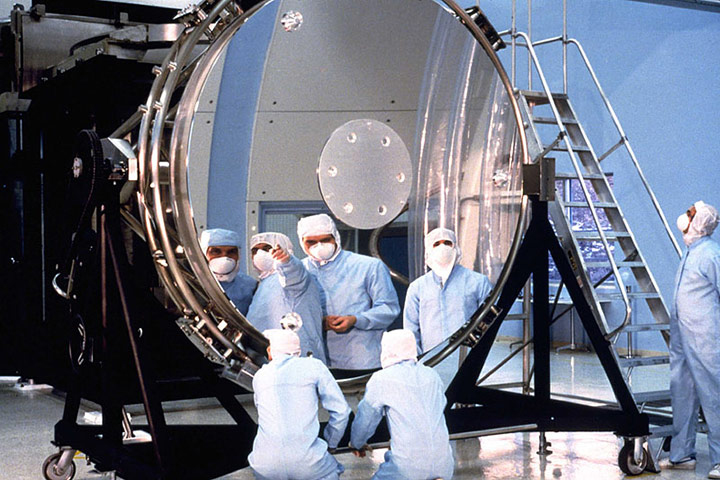 Workers study Hubble's main, eight-foot (2.4 m) mirror. The flaw in the Hubble Space Telescope's optics was due in part to reductions in testing to save money.