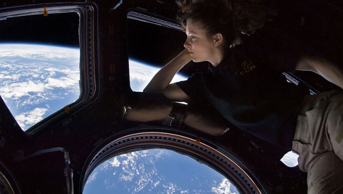 NASA astronaut Tracy Caldwell Dyson, Expedition 24 flight engineer, looks through a window in the Cupola of the International Space Station. A blue and white part of Earth and the blackness of space are visible through the windows. The image was a self-portrait using natural light.