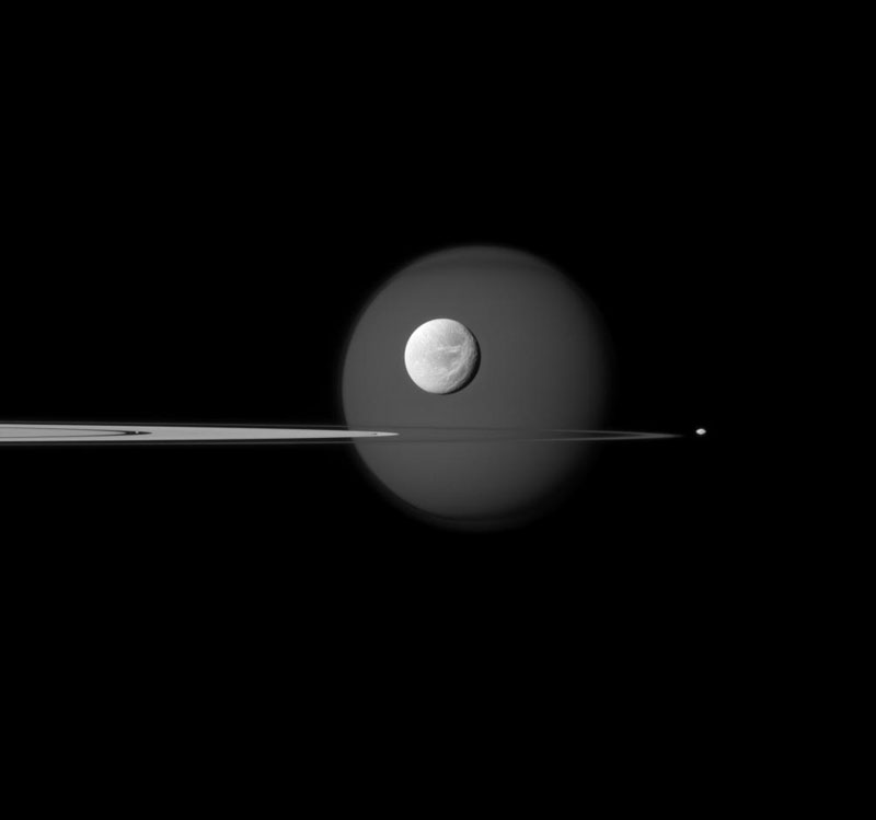 Saturn's largest moon, Titan, is in the background of the image, and the moon's north polar hood is clearly visible. See PIA08137 to learn more about that feature on Titan (3,200 miles, or 5,150 kilometers across). Next, the wispy terrain on the trailing hemisphere of Dione (698 miles, or 1,123 kilometers across) can be seen on that moon which appears just above the rings at the center of the image. See PIA10560 and PIA06163 to learn more about Dione's wisps. Saturn's small moon Pandora (50 miles, or 81 kilometers across) orbits beyond the rings on the right of the image. Finally, Pan (17 miles, or 28 kilometers across) can be seen in the Encke Gap of the A ring on the left of the image. The image was taken in visible blue light with the Cassini spacecraft narrow-angle camera on Sept. 17, 2011.
