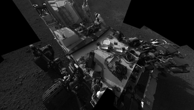 This full-resolution self-portrait shows the deck of NASA's Curiosity rover from the rover's Navigation camera. The back of the rover can be seen at the top left of the image, and two of the rover's right side wheels can be seen on the left. The undulating rim of Gale Crater forms the lighter color strip in the background. Bits of gravel, about 0.4 inches (1 centimeter) in size, are visible on the deck of the rover.