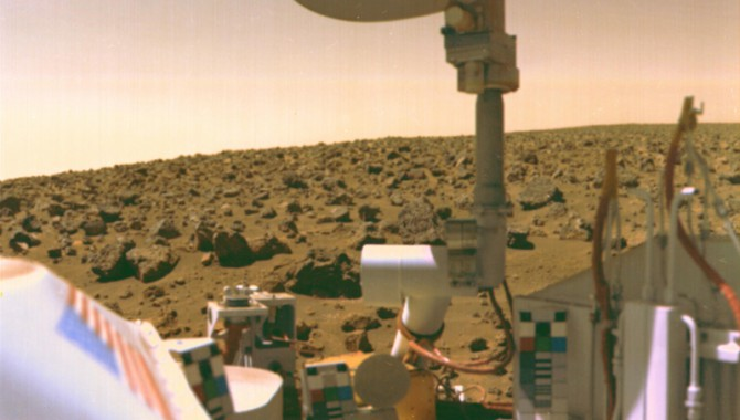 The boulder-strewn field of red rocks reaches to the horizon nearly two miles from Viking 2 on Mars' Utopian Plain. Scientists believe the colors of the Martian surface and sky in this photo represent their true colors. Fine particles of red dust have settled on spacecraft surfaces. The salmon color of the sky is caused by dust particles suspended in the atmosphere. Color calibration charts for the cameras are mounted at three locations on the spacecraft. Note the blue star field and red stripes of the flag. The circular structure at top is the high-gain antenna, pointed toward Earth.Viking 2 landed September 3,1976, some 4600 miles from its twin, Viking 1, which touched down on July 20.