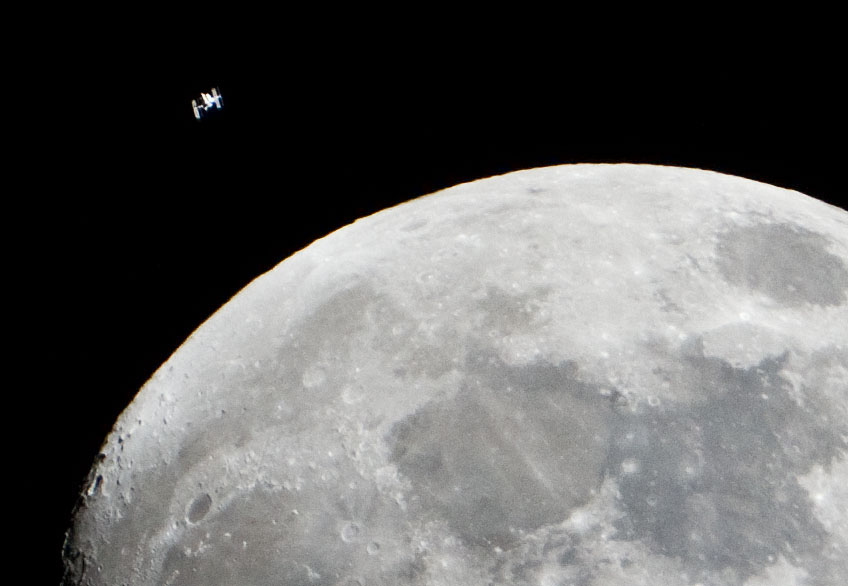 The International Space Station can be seen as a small object in upper left of this image of the moon in the early evening Jan. 4 in the skies over the Houston area flying at an altitude of 390.8 kilometers (242.8 miles).