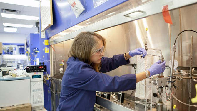 Chemist Anne Caraccio works with a prototype reactor for incinerating trash in space. The device is inside a lab at NASA's Kenendy Space Center in Florida. She is part of the team developing a mechanism to burn trash and extract valuable gases from the material.