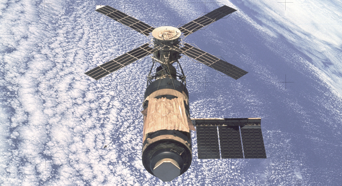 An overhead view of the Skylab Orbital Workshop in Earth orbit as photographed from the Skylab 4 Command and Service Modules (CSM) during the final fly-around by the CSM before returning home. The space station is contrasted against the pale blue Earth.