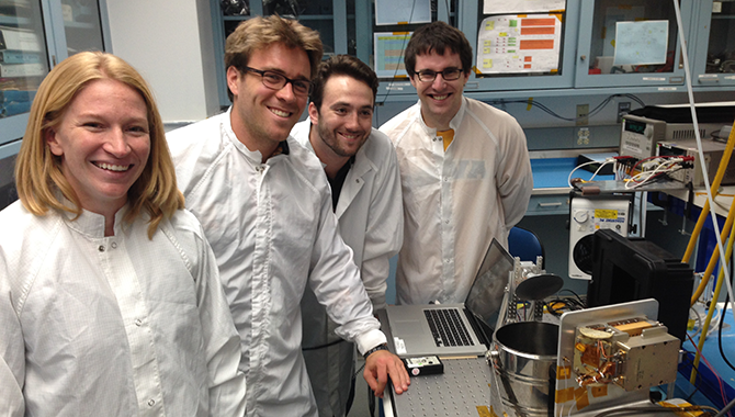 The RACE team members in the lab at the Jet Propulsion Laboratory. From left to right: Shannon Statham, I&T lead; Alex Kadesch, project manager; Joel Steinkraus, instrument cognizant engineer; and Max Bryk, electronics lead. Credit: NASA / Jet Propulsion Laboratory