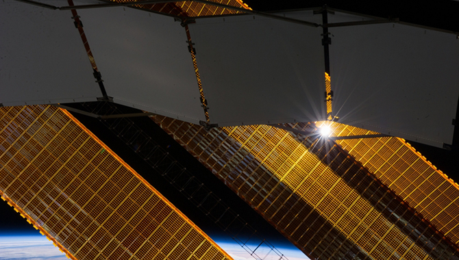A tiny representation of the sun sneaks through between a truss-based radiator panel and a primary solar array panel on the Earth-orbiting International Space Station in this photograph taken by one of the Expedition 38 crew members on Jan. 2, 2014. Clouds over Earth and the blackness of space share the background scene.