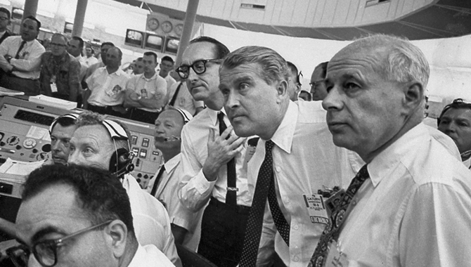 This photograph depicts an intense moment during the SA-6 launch at the Firing Room. Dr. von Braun, Director of the Marshall Space Flight Center (MSFC) is at center; to his left is Dr. George Mueller, Associate Director for Marned Space Flight; and far right is Dr. Eberhard Rees, Director for Research and Development, MSFC. The SA-6, the sixth flight of the Saturn 1 vehicle, launched a S-IV stage (a second stage) and an Apollo boilerplate spacecraft. Photo Credit: NASA