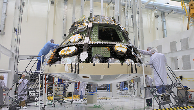 Engineers finalize the installation of the world's largest heat shield on Orion. Photo Credit: NASA/Daniel Casper