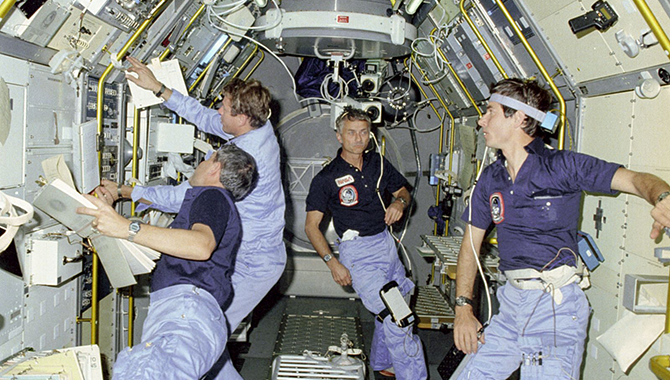 Astronauts conduct scientific research during Spacelab's first mission. From left to right: Mission Specialist Robert Parker, Payload Specialist Byron Lichtenberg, Mission Specialist Owen Garriott, and Payload Specialist Ulf Merbold. Photo Credit: NASA
