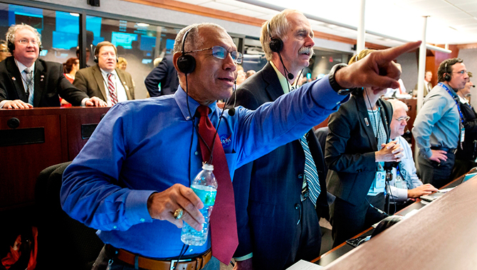 NASA Administrator Charlie Bolden, NASA Associate Administrator for the Human Exploration and Operations Directorate William Gerstenmaier, and others react as Orion splashes down after its inaugural flight. Photo Credit: NASA/Bill Ingalls