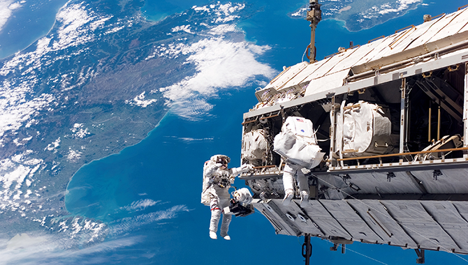 NASA astronaut Robert L. Curbeam Jr. and European Space Agency astronaut Christer Fuglesang participate in an extravehicular activity (EVA) on the ISS. Photo Credit: NASA