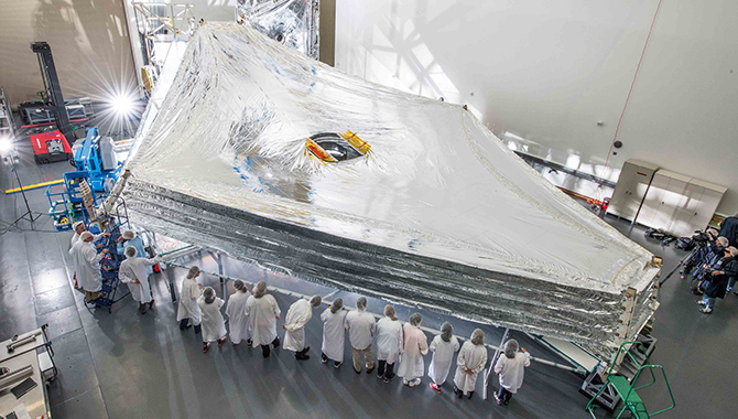 The largest part of the James Webb Space Telescope observatory is the Sunshield, which is roughly the length of a tennis court. It protects the telescope's sensitive infrared instruments, which require extremely cold temperatures to function. Photo Credit: NASA/Chris Gunn