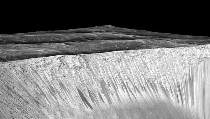 Recurring slope lineae (RSL) are visible on the walls of the Garni Crater on Mars. The RSL are believed to be formed by briny liquid water seeping through the surface of the planet. Photo Credit: NASA/JPL-Caltech/Univ. of Arizona