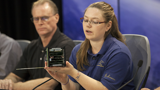 Morgan Johnson, team lead for the University of Alaska Fairbanks satellite, discusses the Alaska Research CubeSat (ARC 1). Cubesats pack all necessary technology into a very small package: a one-unit (1U) cubesat is just 10 centimeters (cm) by 10 cm by 10 cm. Photo Credit: NASA/Kim Shiflett