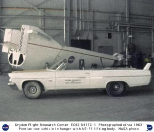 The M2-F1 in its hangar with NASA's muscle car, the Pontiac Catalina convertible tow vehicle. Photo Credit: NASA