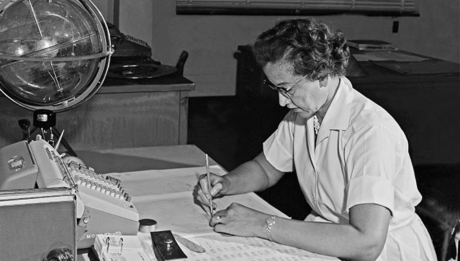 "Research mathematician Katherine Johnson, one of the ""human computers"" whose calculations helped send astronauts safely to the moon, at her desk at Langley Research Center in 1962."