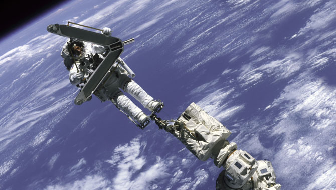 Crew member Lee M. E. Morin participated in his first extravehicular activity (EVA) during STS-110. Here, he is anchored to the station's robotic arm, Canadarm2, which was used for the first time to move astronauts during EVAs. Photo Credit: NASA