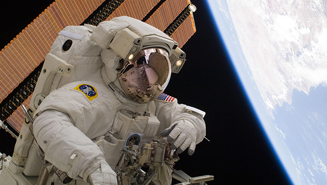 With Earth and one of the station's solar arrays as a backdrop, NASA astronaut Clayton Anderson works during the third spacewalk of the mission. Photo Credit: NASA