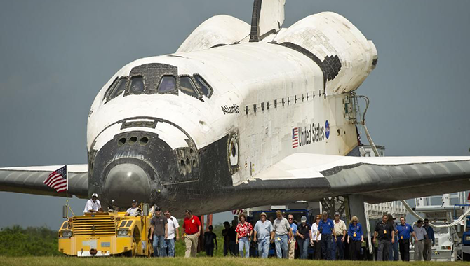 Workers at Kennedy Space Center in Florida accompany shuttle Atlantis as it is towed back to its processing hangar after landing at Kennedy's Shuttle Landing Facility, completing its 13-day mission to the International Space Station and the final flight of the Space Shuttle Program. Photo Credit: NASA/Bill Ingalls