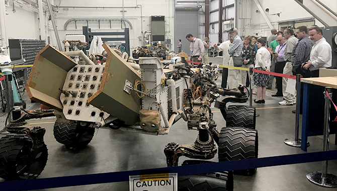 "NASA's knowledge community members tour the facility where ""Maggie"", a test Mars Rover, is being housed before Maggie is moved to the ""Mars Yard""."