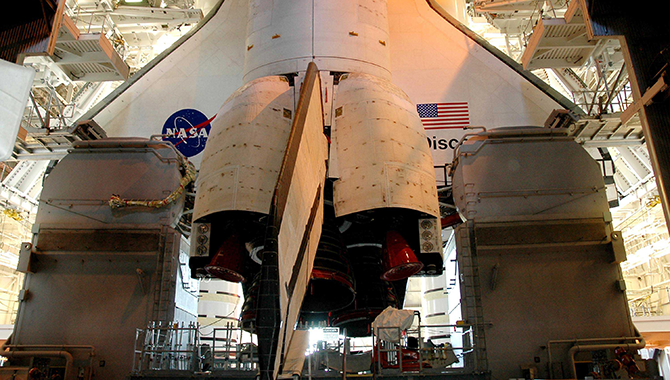 Space Shuttle Discovery in the Vehicle Assembly Building. On either side of Discovery's tail and Orbiter Maneuvering System Pods are the Tail Masts that support the fluid, gas and electrical requirements of the orbiter's liquid oxygen and liquid hydrogen aft T-0 umbilicals. Photo Credit: NASA/KSC