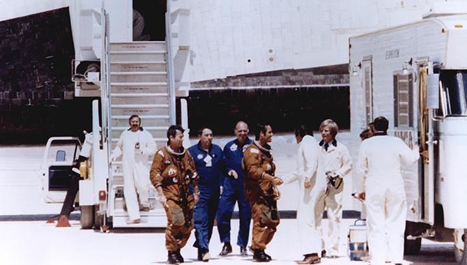 Following the successful landing of the Space Shuttle Columbia, America's first-ever reusable spacecraft, at Edwards Air Force Base on April 14, 1981, STS-1 Commander John Young and Pilot Robert Crippen (in tan space suits) were greeted by members of the ground crew. Credit: NASA