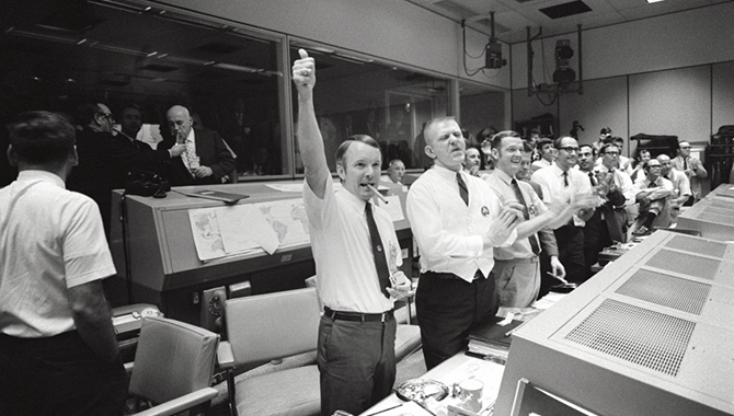 "Members of the highly effective Apollo 13 team applaud the successful splashdown of the command module ""Odyssey."" The group includes three of the four Apollo 13 flight directors (from left to right): Gerald D. Griffin, Eugene F. Kranz, and Glynn S. Lunney. In addition, Dr. Robert R. Gilruth, director, Manned Spacecraft Center (MSC) and Dr. Christopher C. Kraft Jr., MSC deputy director, light up cigars (upper left). Credit: NASA"