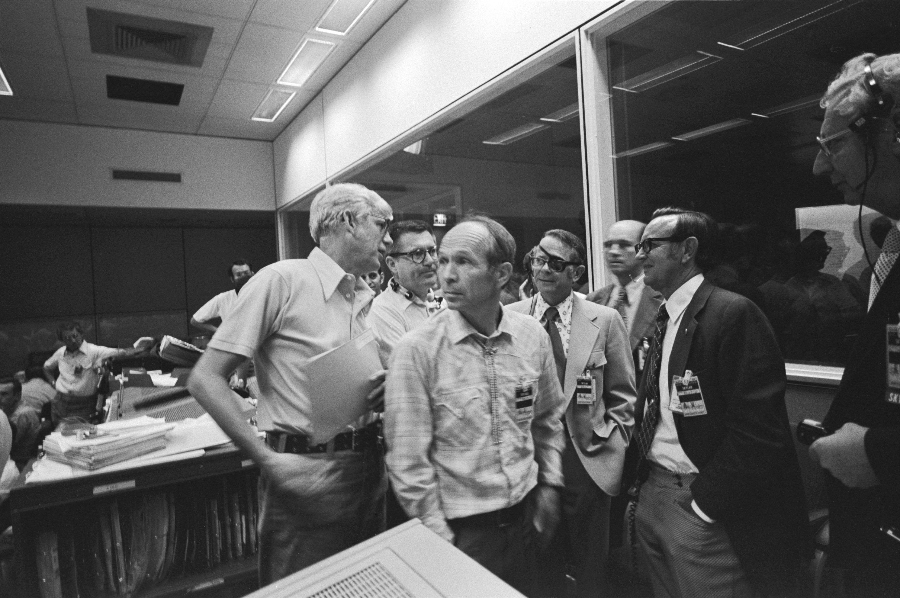 At the Johnson Space Center (JSC) Mission Operations Control Center, NASA officials discuss the problems with the micrometeroid shield on Skylab. From left to right, they include Jack Kinzler, whose Skylab sunshield solution earned him the NASA Distinguished Service Medal, along with William Schneider, Maxim Faget, Dale Myers, JSC Director Chris Kraft, and Kenneth Kleinknecht. Credit: NASA