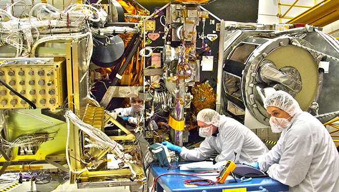 NASA engineers Rob Gallagher (left), Ken Smith (right) and Deneen Ferro (inside the spacecraft, center) work on the GPM Core satellite in the clean room at Goddard Space Flight Center, Greenbelt Md. Credit: NASA