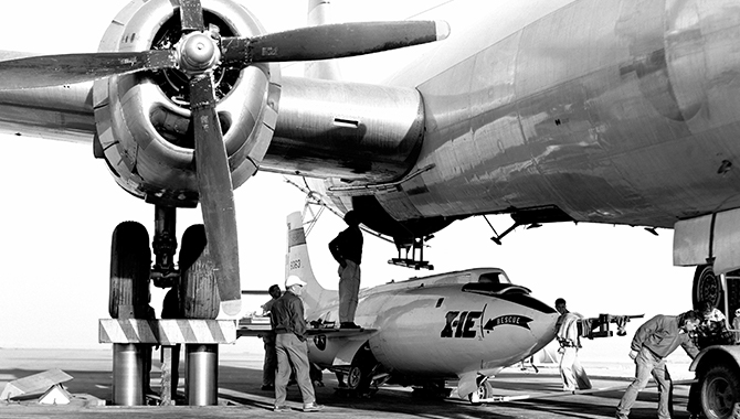 X-1E airplane being loaded under the mothership, Boeing B-29. A hydraulic lift elevated the launch aircraft and then lowered it over the rocket plane for mating. Credit: NASA Photo / NACA/NASA