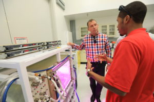 While touring the Space Station Processing Facility at NASA's Kennedy Space Center in Florida, Thomas Zurbuchen, in plaid shirt, NASA's Associate Administrator for the Science Mission Directorate, learns about the advanced habitat used to grow plants in space. Credit: NASA