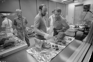 Astronaut Edgar D. Mitchell (left), lunar module pilot, holds up a tote bag in which some of the lunar samples were stowed, while astronaut Alan B. Shepard Jr., commander, looks on. Credit: NASA
