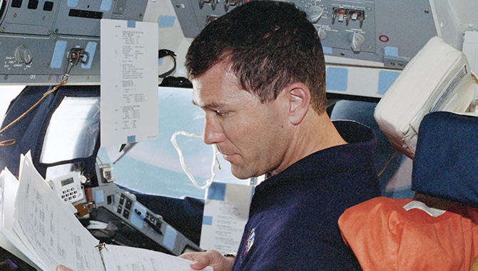 Astronaut Rick D. Husband, pilot, reads over the flight data file at the pilot's station on the starboard side of Discovery's forward cabin during a mission in 1999. Credit: NASA
