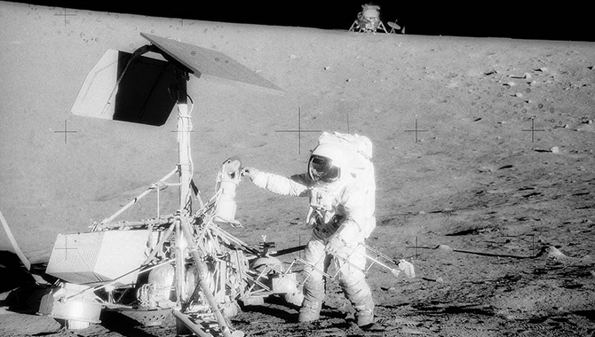 "Commander Charles ""Pete"" Conrad Jr. examines the TV camera of Surveyor 3 prior to detaching it and returning it, and other pieces of the lander, to Earth for analysis. Credit: NASA"