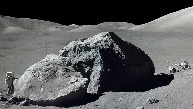 Harrison H. Schmitt examines a boulder during the Apollo 17 mission. The Lunar Roving Vehicle (LRV), which transported Schmitt and Eugene A. Cernan to this site, is seen in the background. Credit: NASA/Eugene Cernan