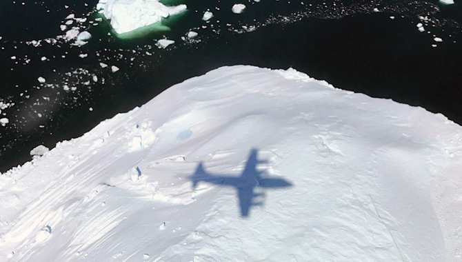 The shadow of NASA's P-3 aircraft is seen over an iceberg on a May 8, 2017 flight. The plane, which carries sophisticated technology, will fly through snowstorms on the U.S. East Coast in a three-year project to better understand how snow bands form. Credit: NASA/Joe MacGregor