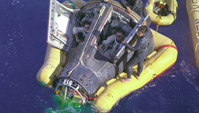 Astronauts Neil Armstrong and David R. Scott sit with their spacecraft hatches open while awaiting the arrival of the recovery ship, the U.S.S. Leonard F. Mason, after the completion of their Gemini VIII mission. Credit: NASA